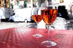 Dos vidrios de vino rojo en la tabla de un café de la calle en un día soleado brillante Fotografía de archivo