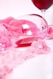 Dos vidrios de vino rojo en un fondo blanco de las bragas alrededor de rosadas Imagen de archivo libre de regalías