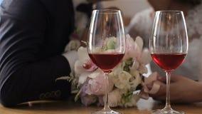 Dos vidrios de vino rojo en un fondo de los pares hermosos de la boda Cámara lenta almacen de metraje de vídeo