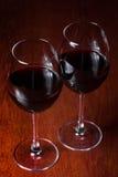 Dos vidrios de vino rojo en un fondo oscuro Foto de archivo