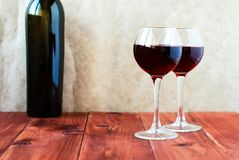 Dos vidrios de vino rojo en un vector de madera Imagen de archivo libre de regalías