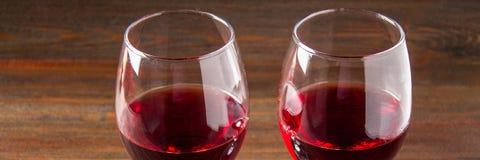 Dos vidrios de vino rojo en una tabla de madera marrón Bebidas alcohólicas bandera Imagenes de archivo