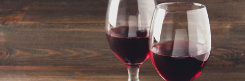 Dos vidrios de vino rojo en una tabla de madera marrón Bebidas alcohólicas bandera Fotos de archivo