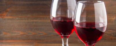 Dos vidrios de vino rojo en una tabla de madera marrón Bebidas alcohólicas bandera Foto de archivo