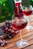 Dos vidrios de vino rojo hecho en casa delicioso con la uva Foto de archivo libre de regalías