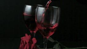Dos vidrios de vino rojo que es vertido con la rosa del rojo almacen de metraje de vídeo