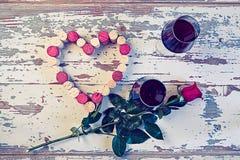 Dos vidrios de vino rojo y de un corazón con los corchos Foto de archivo libre de regalías