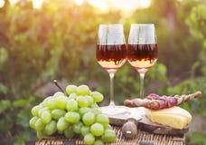Dos vidrios de vino rosado con pan, carne, la uva y el queso Imagen de archivo
