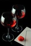 Dos vidrios de vino, un corazón y una carta de la oferta Foto de archivo libre de regalías