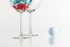 Dos vidrios de vino y de equipos de golf Fotografía de archivo