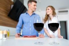 Dos vidrios de vino y de pares felices que se colocan en cocina Foto de archivo libre de regalías