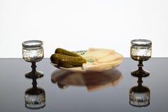 Dos vidrios de vodka con manteca de cerdo y pepinos en una placa Imágenes de archivo libres de regalías