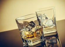 Dos vidrios de whisky en la tabla con la reflexión, atmósfera caliente Imagen de archivo
