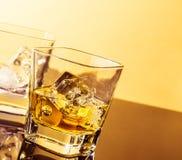 Dos vidrios de whisky en la tabla con la reflexión, atmósfera caliente Fotos de archivo libres de regalías