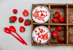 Dos vidrios de yogur, fresas frescas rojas en la caja de la rota con las cucharas plásticas en el Libro Blanco Desayuno TA sana o Fotografía de archivo