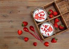 Dos vidrios de yogur, fresas frescas rojas en la caja de la rota con las cucharas plásticas en la tabla de madera Desayuno T sano Imagenes de archivo