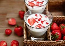 Dos vidrios de yogur, fresas frescas rojas en la caja de la rota en la tabla de madera Comida sabrosa orgánica del desayuno Cocin Imagen de archivo libre de regalías