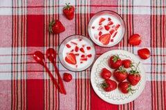 Dos vidrios de yogur, las fresas frescas rojas están en la placa de cerámica con las cucharas plásticas en el mantel del control  Fotos de archivo