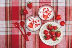 Dos vidrios de yogur, las fresas frescas rojas están en la placa de cerámica con las cucharas plásticas en el mantel del control  Imagen de archivo libre de regalías