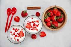 Dos vidrios de yogur, las fresas frescas rojas están en la placa de madera con las cucharas plásticas, canela en el Libro Blanco  Foto de archivo libre de regalías