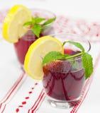 Dos vidrios de zumo de fruta rojo con el limón fotos de archivo libres de regalías