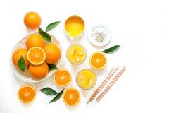 Dos vidrios de zumo de naranja con los cubos y las naranjas de hielo aislados en la opinión superior del fondo blanco Fotos de archivo libres de regalías