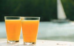 Dos vidrios de zumo de naranja contra el mar Foto de archivo