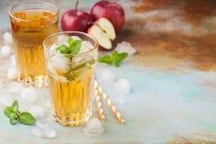 Dos vidrios de zumo de manzana rojo con la menta y el hielo en una tabla oxidada vieja Refresco en un fondo azul Con el espacio d Imagen de archivo libre de regalías