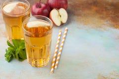 Dos vidrios de zumo de manzana rojo con la menta y el hielo en una tabla oxidada vieja Refresco en un fondo azul Con el espacio d Foto de archivo