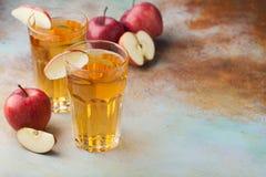 Dos vidrios de zumo de manzana rojo con la menta y el hielo en una tabla oxidada vieja Refresco en un fondo azul Con el espacio d Imágenes de archivo libres de regalías