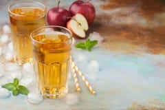 Dos vidrios de zumo de manzana rojo con la menta y el hielo en una tabla oxidada vieja Refresco en un fondo azul Con el espacio d Fotografía de archivo