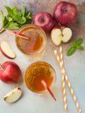 Dos vidrios de zumo de manzana rojo con la menta y el hielo en una tabla oxidada vieja Refresco en un fondo azul Visión superior Imagenes de archivo