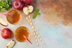 Dos vidrios de zumo de manzana rojo con la menta y el hielo en una tabla oxidada vieja Refresco en un fondo azul Visión superior  Foto de archivo libre de regalías