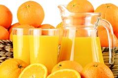 Dos vidrios de zumo y de frutas de naranja Imágenes de archivo libres de regalías
