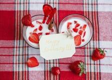 Dos vidrios del cóctel de la leche, fresas frescas rojas en el mantel del control Tarjeta de cumpleaños del deseo Desayuno Foo sa Imagen de archivo