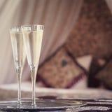 Dos vidrios del champán con el toldo oriental acuestan en el fondo Imagen de archivo