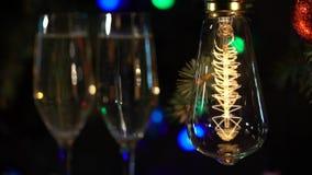 Dos vidrios del champán de las bombillas de la guirnalda multicolora de la atmósfera festiva metrajes