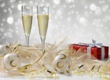 Dos vidrios del champán, decoración de oro Regalo rojo con el ri blanco Imagenes de archivo
