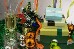 Dos vidrios del champán en bokeh de la Navidad con nieve, las luces, el abeto y las cajas de regalo en fondo azul Imagen de archivo