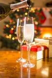 Dos vidrios del champán en la tabla que es llenada de la botella imagenes de archivo
