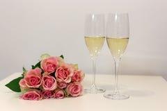 Dos vidrios del champán y de un ramo hecho de rojo claro hermoso/se ruborizan las rosas rosadas Fotografía de archivo