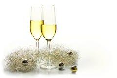 Dos vidrios del champán de las flautas por Año Nuevo y la decoración de oro Imagen de archivo libre de regalías