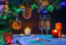 Dos vidrios del shampagne con los candeles y el árbol de navidad Fotografía de archivo libre de regalías