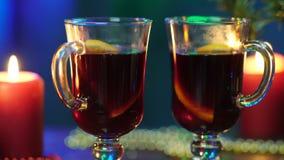 Dos vidrios del soporte reflexionado sobre del vino en un fondo borroso de un árbol de navidad, de luces de la Navidad coloridas  almacen de video