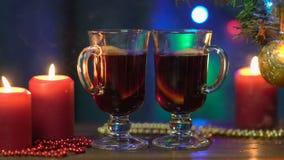 Dos vidrios del soporte reflexionado sobre del vino en un fondo borroso de un árbol de navidad, de luces de la Navidad coloridas  almacen de metraje de vídeo