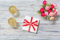 Dos vidrios del vino blanco, de flores y de un regalo Fotos de archivo libres de regalías