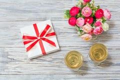 Dos vidrios del vino blanco, de flores y de un regalo Imagenes de archivo