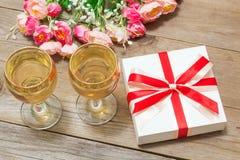 Dos vidrios del vino blanco, de flores y de un regalo Foto de archivo libre de regalías