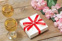 Dos vidrios del vino blanco, de flores y de un regalo Imagen de archivo