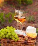 Dos vidrios del vino blanco, diversas clases de queso y uvas en el th Fotos de archivo